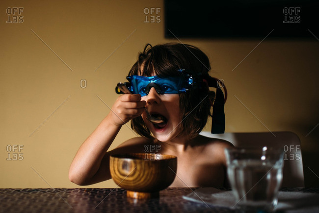 Young girl wearing night vision glasses and taking bite of cereal
