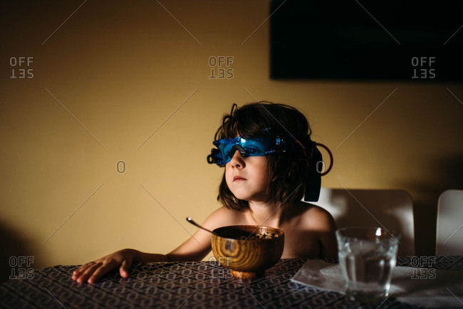 Young girl wearing night vision glasses and eating cereal