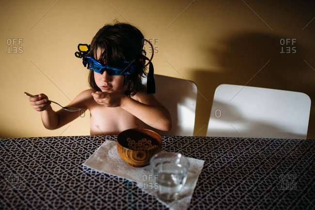 Young girl eating cereal while wearing night vision glasses