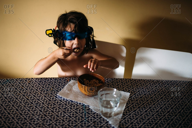 Young girl taking bite of cereal while wearing night vision glasses