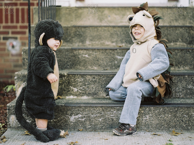 Two little boys dressed up for Halloween playing on steps