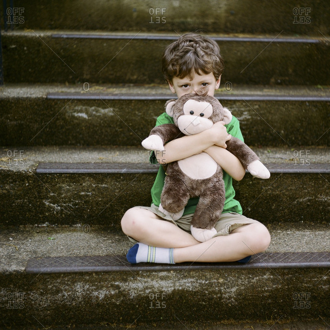 Boy on steps holding stuffed monkey