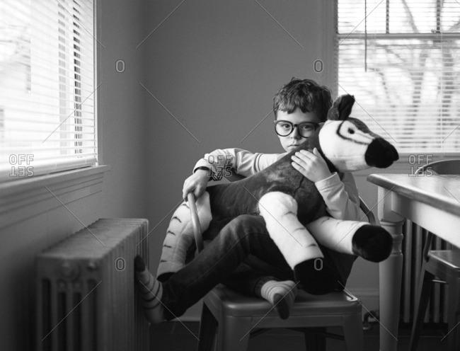 Boy on chair holding stuffed okapi