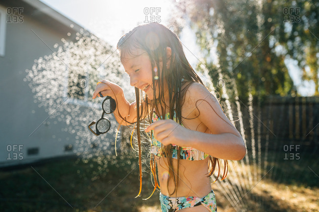 Laughing girl playing in sprinklers