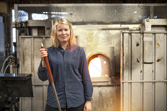 A female glass blower by furnace