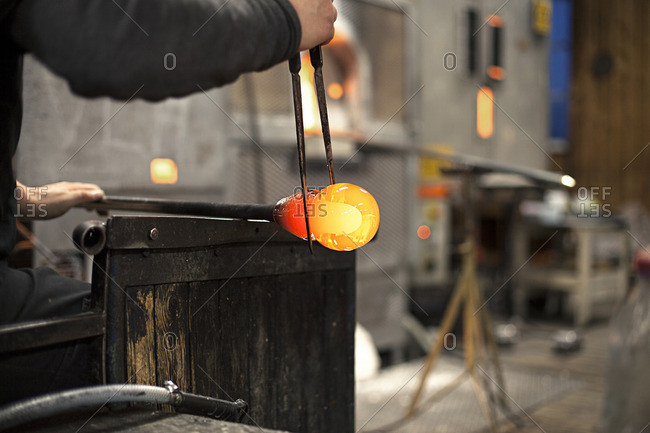 Glass blower shaping hot glass