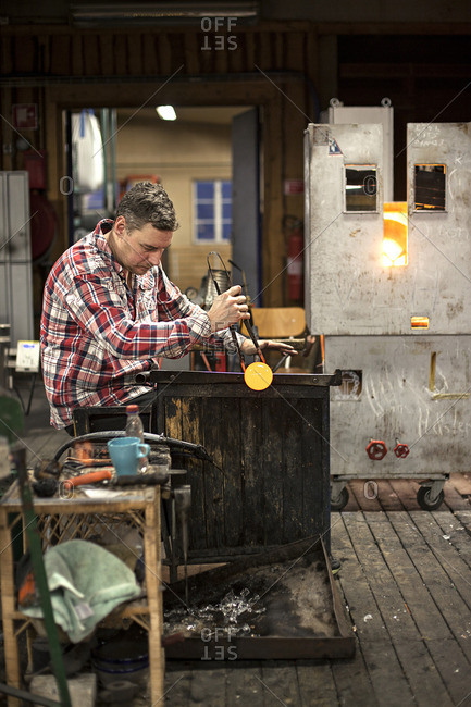 A man shaping hot glass