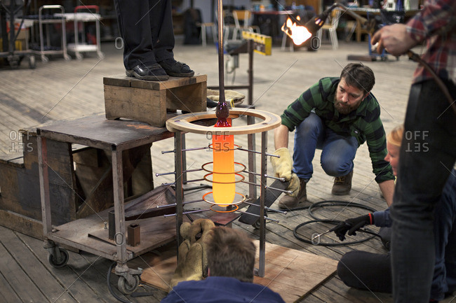 Glass makers shaping a glass piece