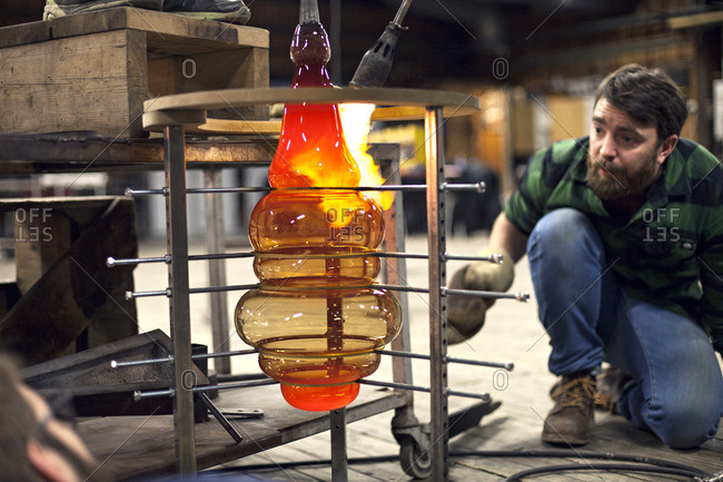 Glass maker watching piece being formed