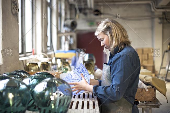 Glass maker inspecting bowl