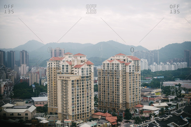 Guangdong Province, China - November 2, 2015: Apartment buildings by mountains