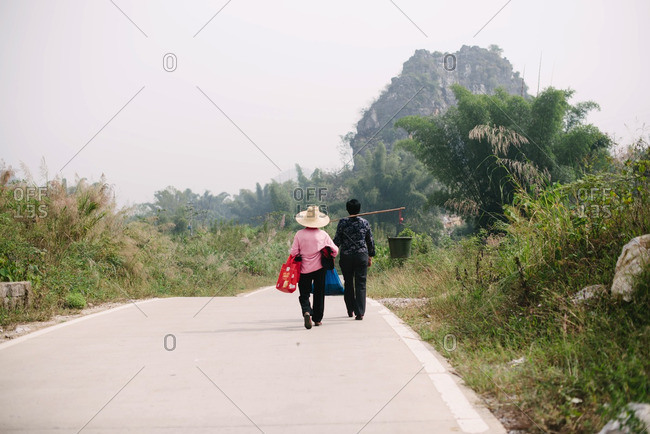 Guangxi, China - November 4, 2015: Woman walking rural road