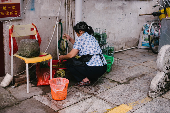 China - November 6, 2015: Woman washing vegetables in market
