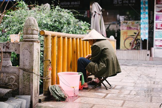 China - November 6, 2015: Person fishing off city street