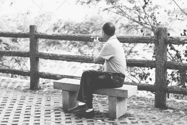 Man smoking cigar on bench