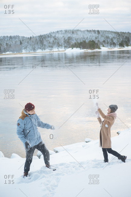 A pair throwing snowballs at each other near water in winter