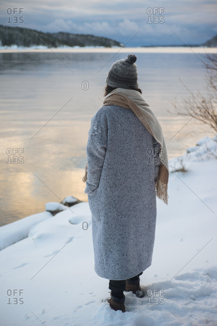 Back view of woman holding hands in pocket looking at waterscape