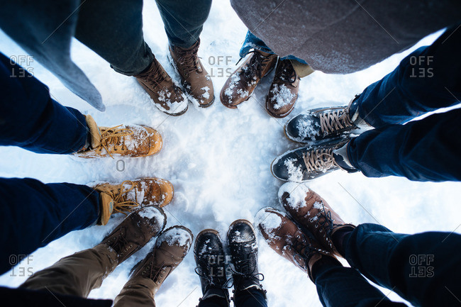 Crop shot of young friends in winter shoes and outwear standing around together on snow