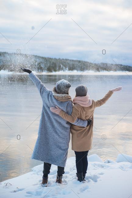 Women throwing snowballs to lake