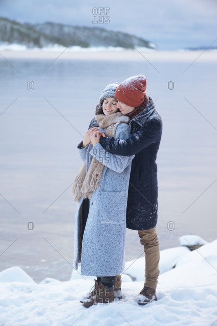 Photo of young attractive couple in winter clothes hugging on winter nature