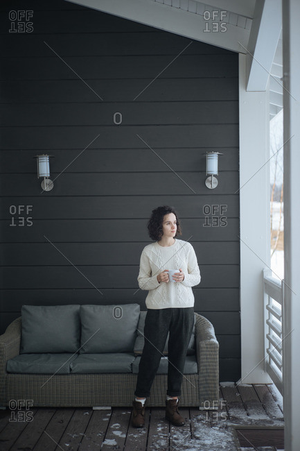 Shot of stylish female in sweater holding cup and standing on winter terrace