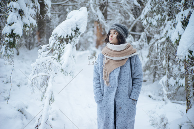 Portrait of a pretty young lady in long coat and scarf having small walk along snow-dusted forest