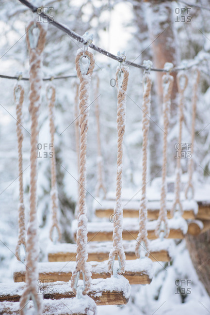 Small wooden hanging bridge covered in snow dusting against a blurry background of a winter forest
