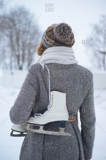 Back view of girl in winter clothes standing with skates with winter nature on background