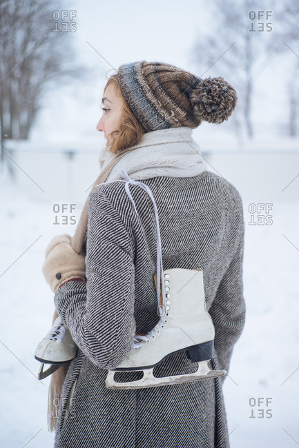Young girl in winter clothes standing with skates with snowbound forest on background