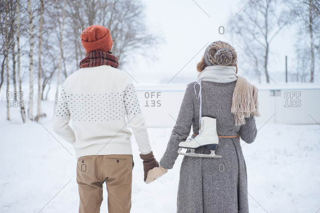 Back view of couple walking in snow forest with skates