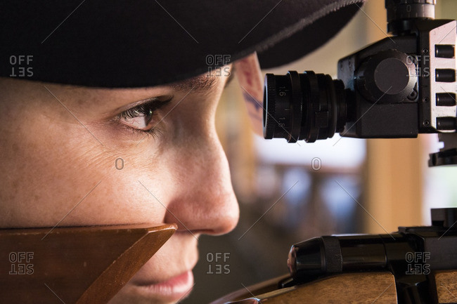 Woman with a sporting rifle aiming in a shooting range