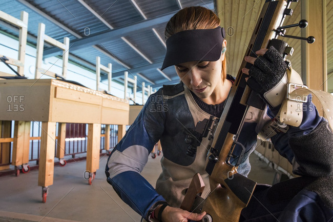 Woman examining her sporting rifle in a shooting range