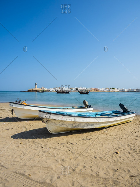 Oman- Ash Sharqiyah- Ad Daffah- two motorboats lying on beach of seaport Sur