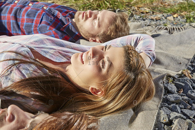 Young couple lying on a blanket outdoors