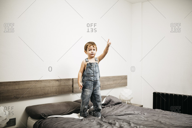 Little boy standing on the bed of his parents pointing on something