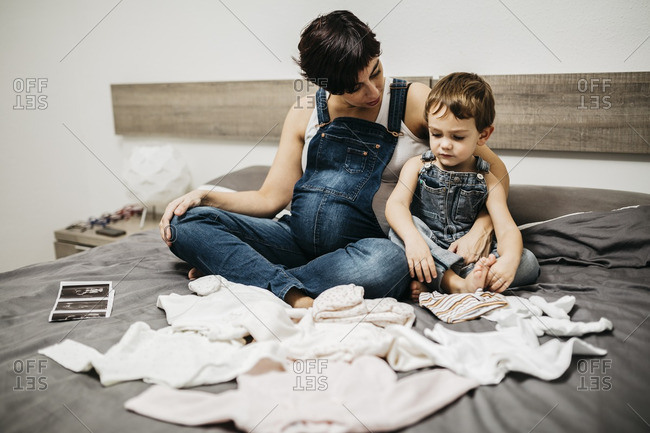 Pregnant woman and her little son sitting together on bed with baby clothing