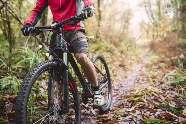 Young man mountain biking in forest
