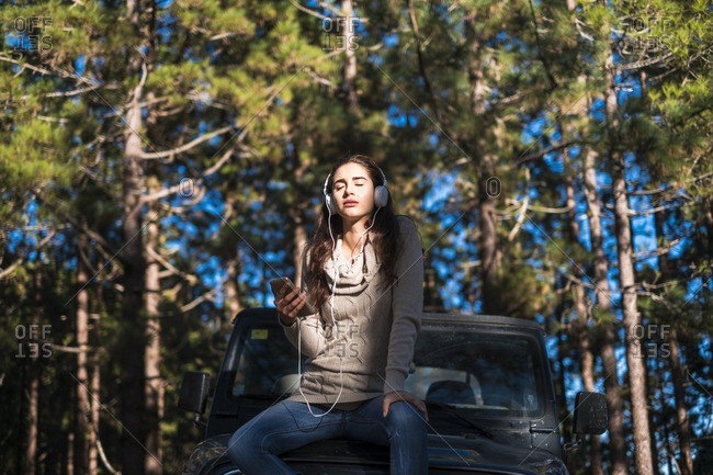 Young woman with eyes closed sitting on car bonnet in the forest listening music with headphones