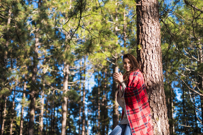 Smiling young woman with blanket and beverage leaning against tree trunk in the forest