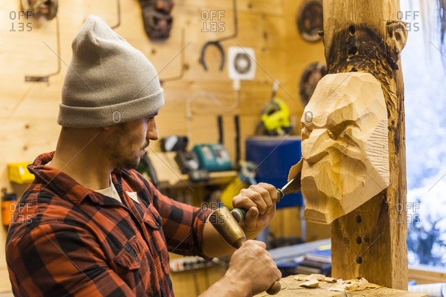 Wood carver manufacturing traditional Krampus mask