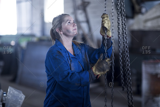 Woman pulling a chain in workshop
