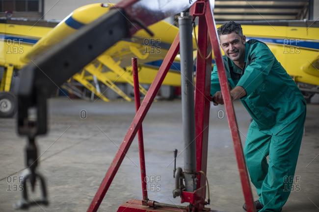 Mechanic in hangar repairing light aircraft
