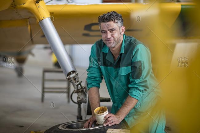 Mechanic in hangar lubricating landing gear of light aircraft
