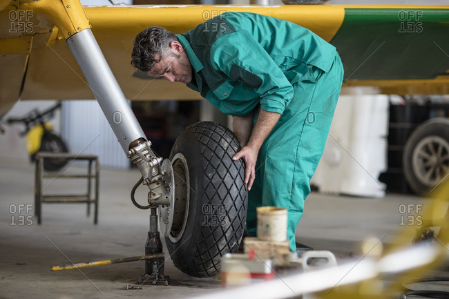 Mechanic in hangar repairing light aircraft- fixing tire