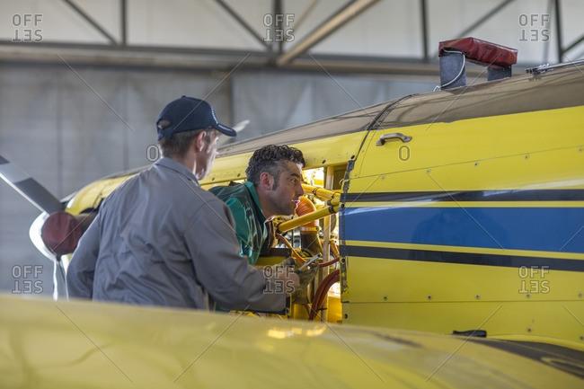 Mechanics in hangar repairing light aircraft