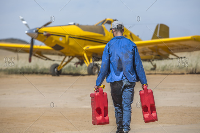 Mechanic carrying jerry cans towards yellow crop dusting plane