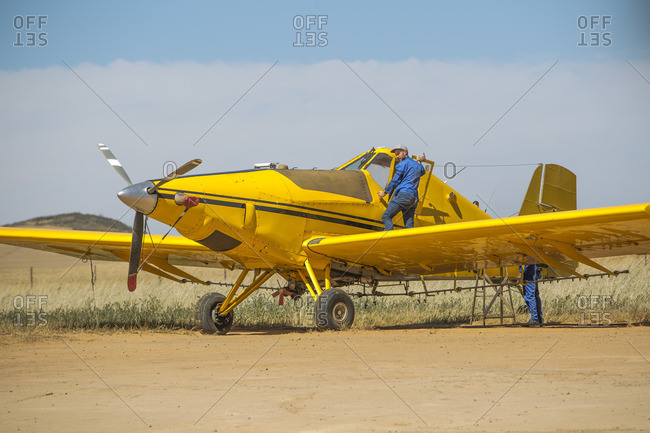 Mechanics preparing yellow crop dusting plane