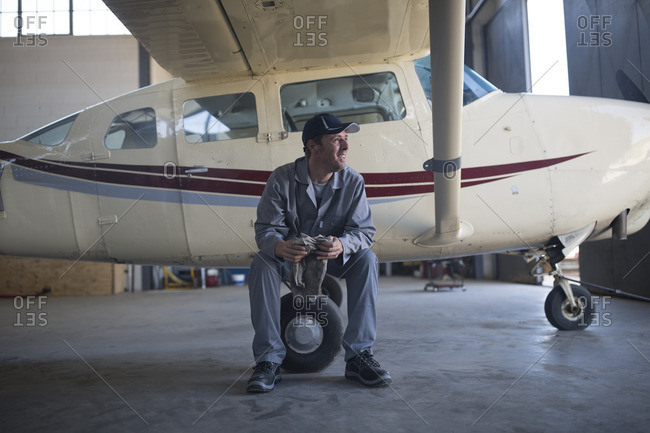 Mechanic sitting next to light aircraft in airfield hangar