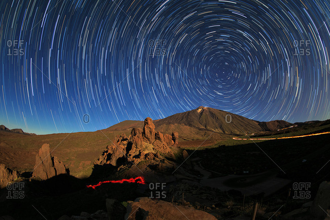 Long exposure of star trails around the North Celestial Pole at moonrise over Mount Teide volcano