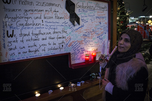 Berlin, Germany - December 20, 2016: A woman signs a remembrance board the day after the terrorist attack in Berlin, Germany, on the 19th of December 2016
